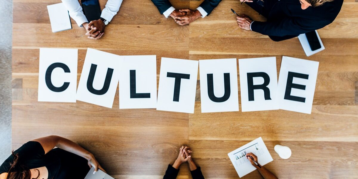 Group of business people with alphabets signs forming the word Culture on table. Top view of business people discussing over work culture in a meeting.